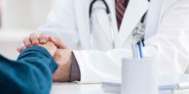 médico e paciente dando as mãos