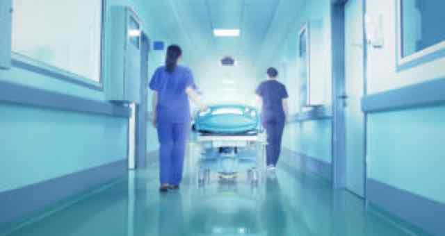 paciente em maca sendo levado por médicas no corredor do hospital