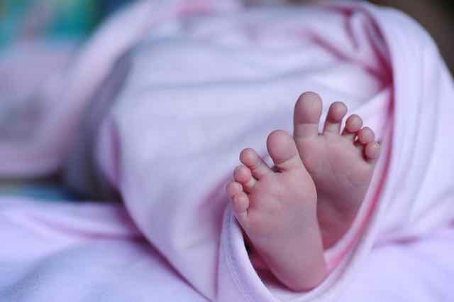 pés de um bebê enrolado em uma manta rosa