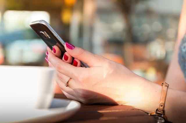 mulher usando o celular enquanto toma um café
