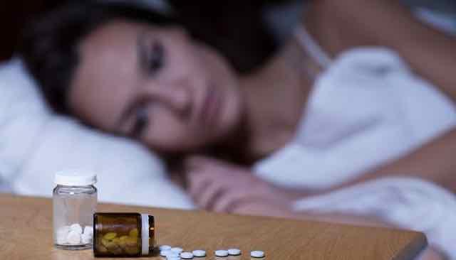 mulher deitada na cama tomando pilulas pra dormir