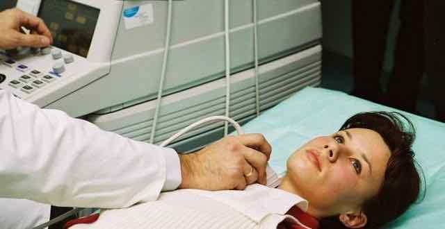 médico realizando ultrassonografia em paciente