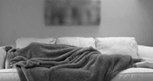 pessoa coberta dormindo no sofá