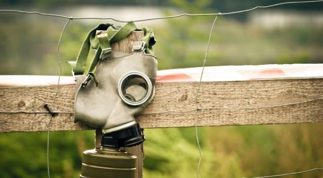 mascara de gas pendurada em uma cerca