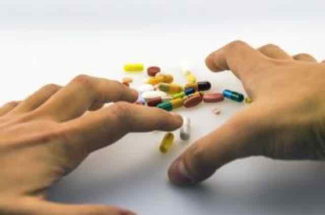 mãos tentando pegar pilulas