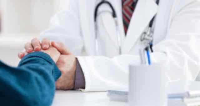 médico segurando a mão de um paciente