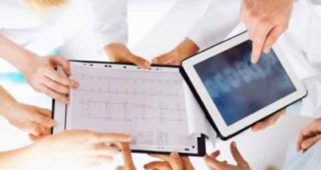 grupo de médicos olhando para um ECG