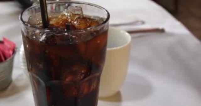 copo com refrigerante e gelo em cima da mesa