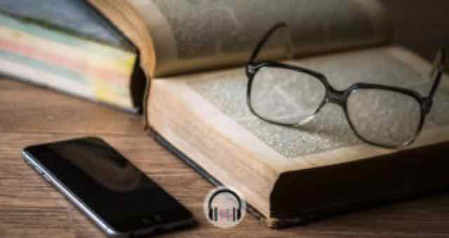 óculos em cima de um livro com um celular do lado