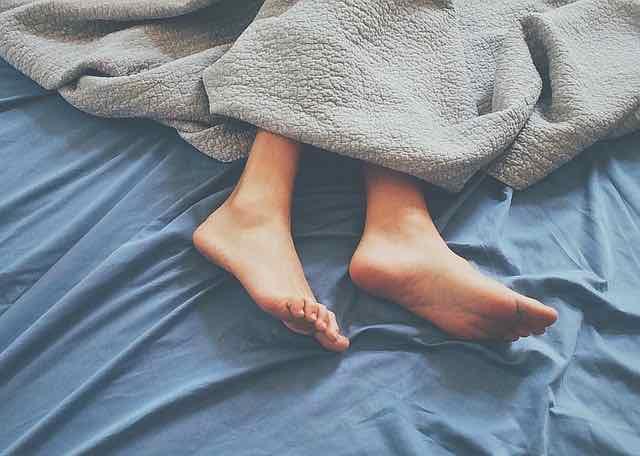 pessoa dormindo com os pés para fora do lençol
