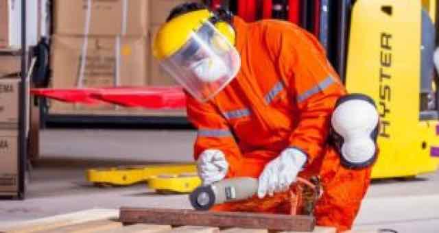 homem agachado trabalhando com uma serra