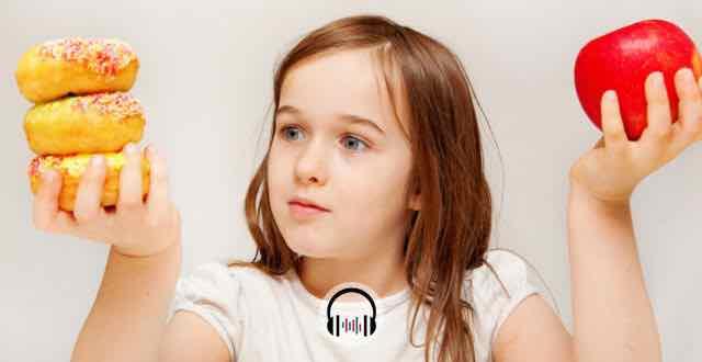 criança com uma maçã em uma mão e donuts em outra
