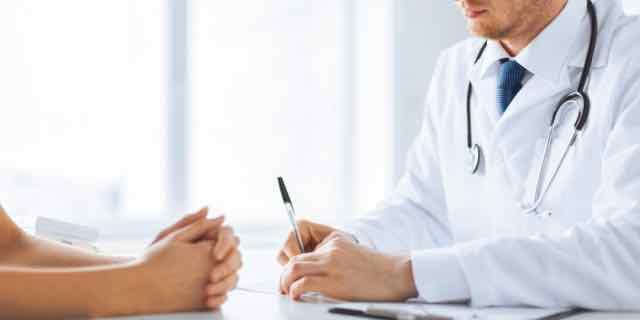 close de paciente e médico tomando notas