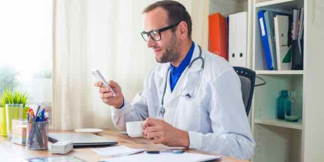 médico usando o celular no consultório