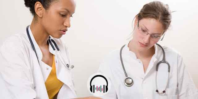 duas medicas olhando para livros e conversando