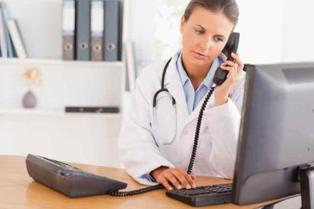 médica no telefone em seu consultório