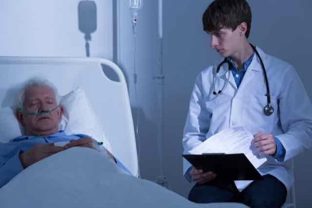 médico observando paciente com doença terminal no leito