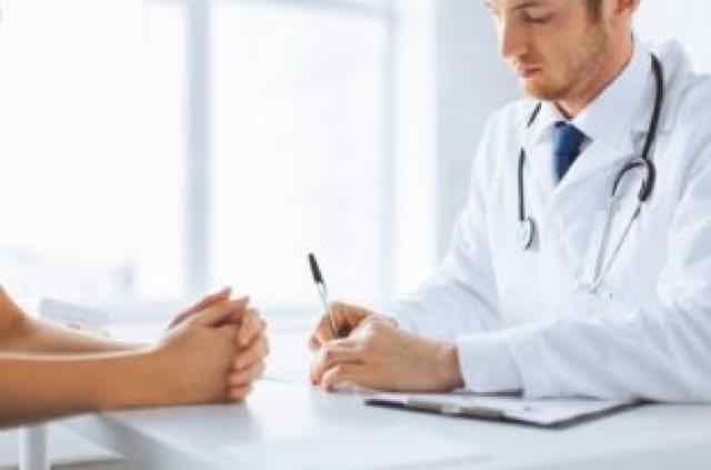 close de paciente e médico anotando