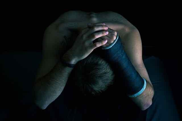 homem com a cabeça baixa, em depressão