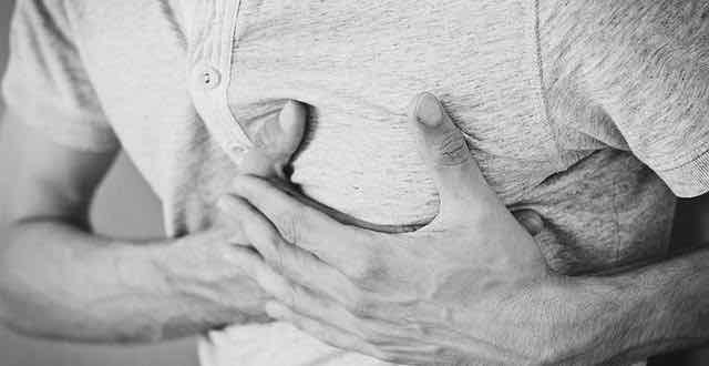 homem com as duas mãos sobre o peito com dor