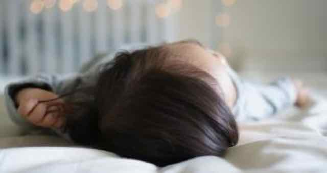 criança vista de cima dormindo na cama