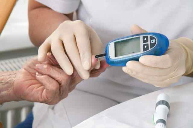 enfermeira medindo glicemia de paciente