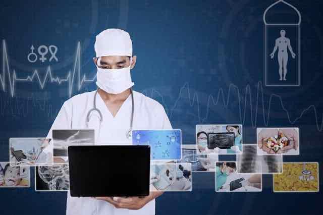 medico de branco trabalhando no computador