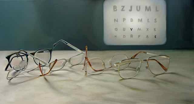 oculos em cima da mesa e tabela com letras no fundo