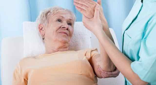 idosa com dores no braço sendo examinada