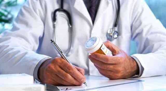 medico segurando um remedio e escrevendo uma prescricao