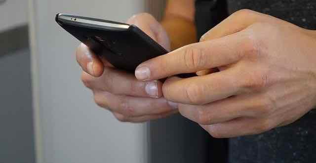 close de mão com celular na mão