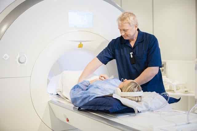 radiologista preparando paciente para tomografia