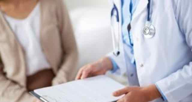 médica segurando ficha na consulta com paciente
