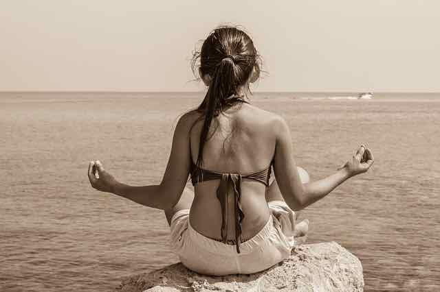 menina meditando em pedra
