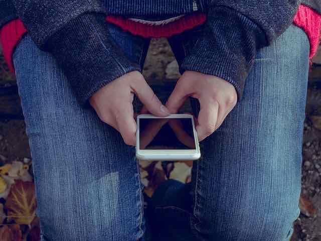 mulher sentada segurando um iphone