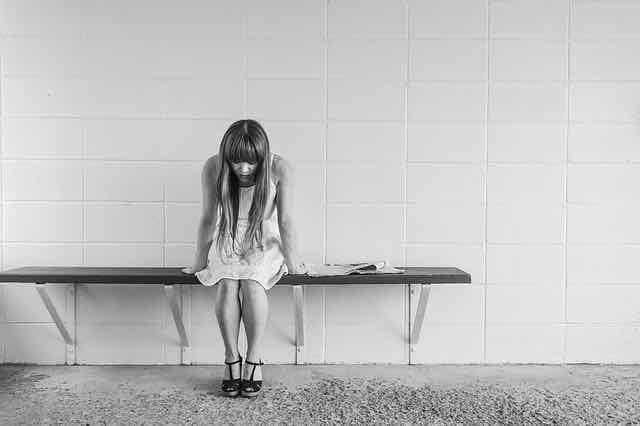 imagem em preto e branco de menina sentada em banco com cabeça baixa
