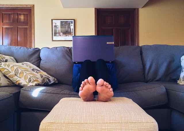 pessoa sentada no sofá com computador no colo