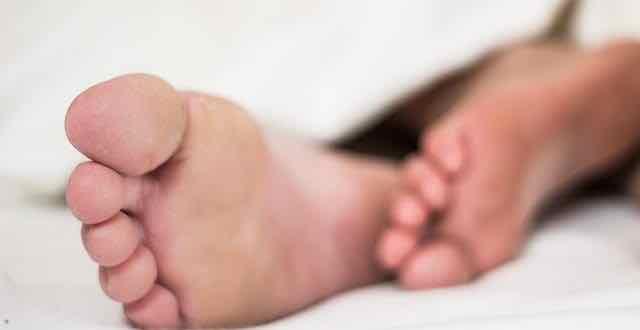 close de pés em uma cama