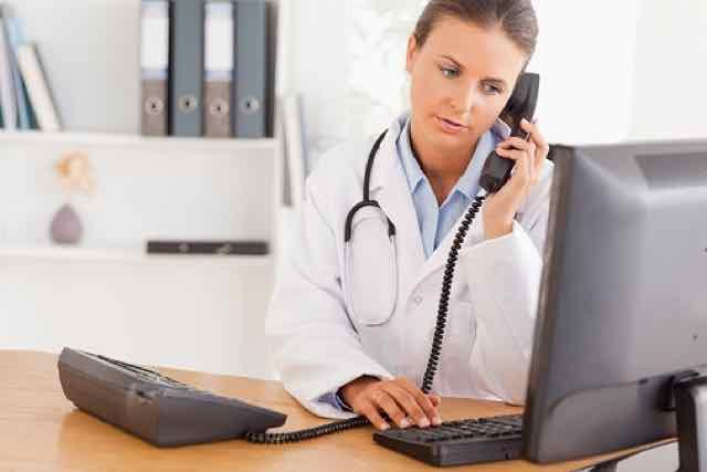 médico no consultório falando no telefone