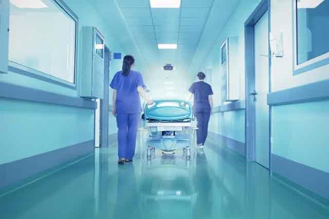 corredor com duas enfermeiras levando uma maca