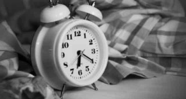 despertador em uma cama em preto e branco