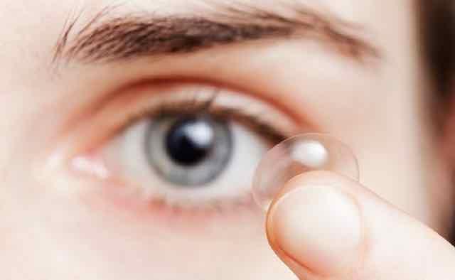 mulher segurando uma lente de contato no dedo