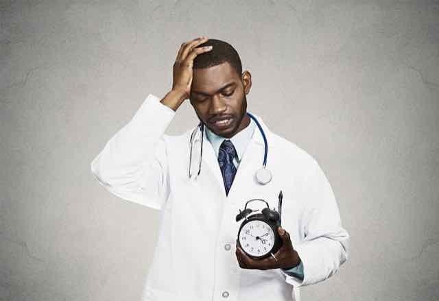 homem estressado segurando um relógio