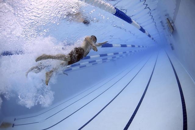 homem nadando em piscina olímpica