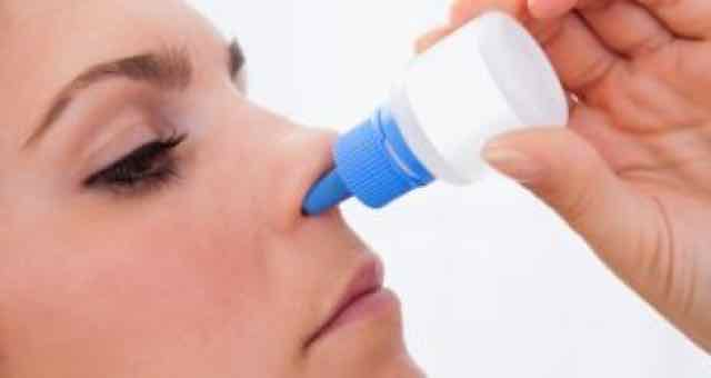 mulher usando um spray nasal