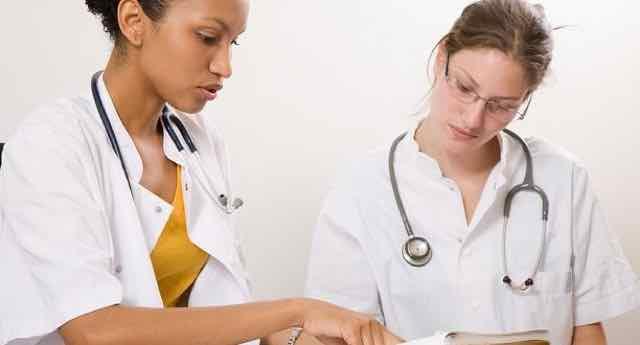 duas estudantes de medicina olhando livros