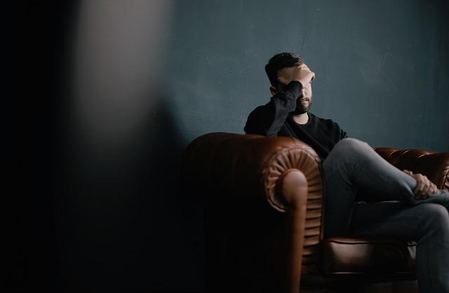 homem sentado com mão na cabeça
