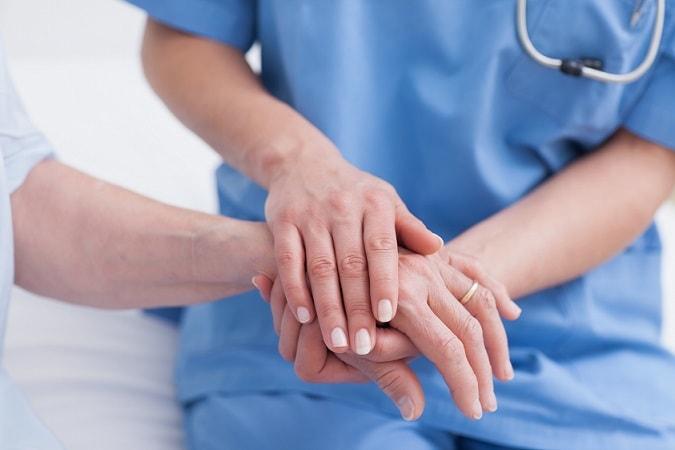enfermeiro tocando a mão de paciente com hanseníase