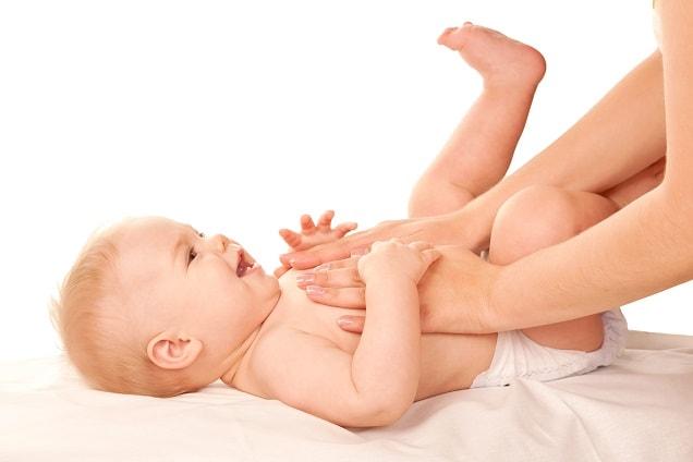 bebê com febre deitado, com mãos de um adulto em cima do peito