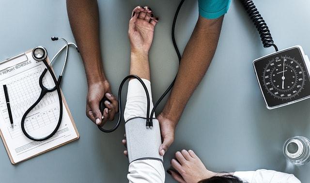 enfermeiro aferindo pressão de paciente com hipertensão